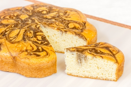 crusted: A closeup view of a marble cake and a slice of it  The marble cake is similar to a pound cake but has random chocolate swirls on it