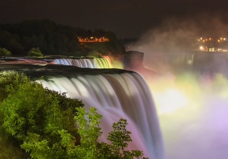 The Niagara falls being beautifully illuminated by colorful lights at night  photo