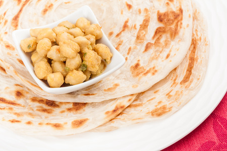 Homemade parotta  Indian bread  served with delicious Indian chana masala  It is prepared using chana dal  chickpea  and various spices  photo