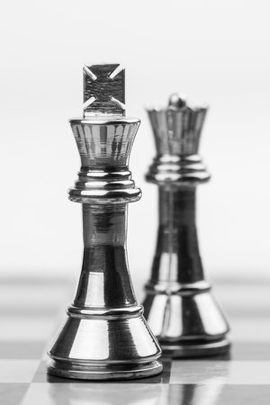 chess king: Rugged brass chess king and queen pieces on a chess board  Shallow DOF used for emphasis of powerful king