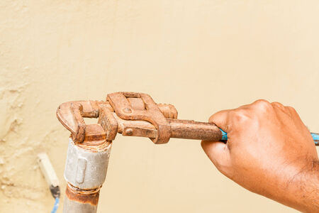 Closeup view of a wrench in the hands of a plumber  photo