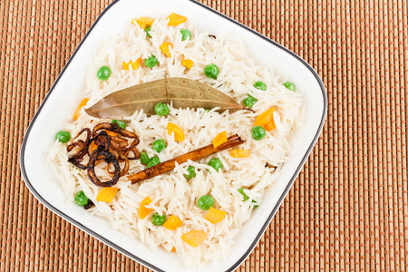 Closeup view from the top of delicious vegetable pulao garnished with bay leaf, cinnamon stick and fried onion. Stock Photo