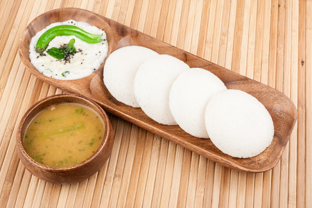 close up food: A traditional ethnic south Indian breakfast of Idly (Idli  rice cake) served with coconut chutney and sambar.