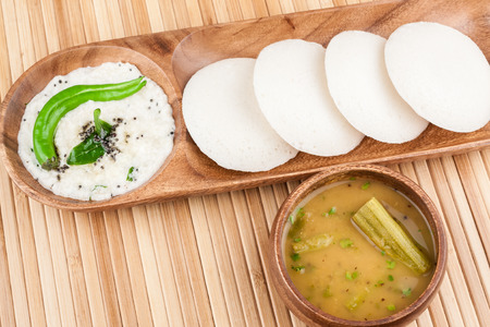 A traditional ethnic south Indian breakfast of Idly (Idli / rice cake) served with coconut chutney and sambar.