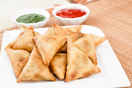 Closeup view of delicious deep fried south Indian samosa with mint chutney and tomato sauce.