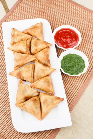 the deep south: Overhead view of delicious deep fried south Indian samosa with mint chutney and tomato sauce. Stock Photo