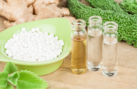 A homeopathy concept with homeopathic medicine (sugarlactose pills and liquid homeopathic substances) pictured along with homeopathic vegetables and herbs on a wooden tabletop. photo