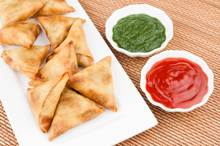 chutney: Overhead view of delicious deep fried south Indian samosa with mint chutney and tomato sauce. Stock Photo