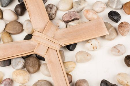 beautiful jesus: Palm Cross - Palm Cross set on multi colored stones. Background for Easter, Good Friday or Palm Sunday.