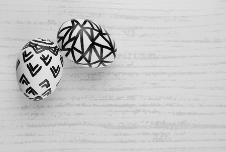 black and white line drawing: Easter Eggs in Black and White - Natural eggs with free hand sketch patterns set on a tile background for Easter. Black and white image.