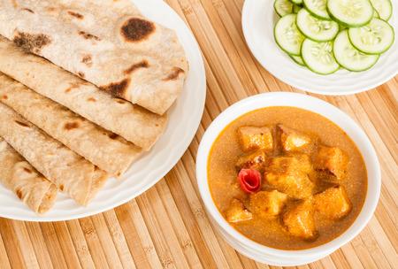 comida gourmet: Chapati con india Paneer Mantequilla Masala - chapati trigo casera doblado (pan indio) servido con deliciosa Indian Masala paneer mantequilla y ensalada de pepino. Se prepara usando paneer (reques�n), mantequilla, tomate y diversas especias.
