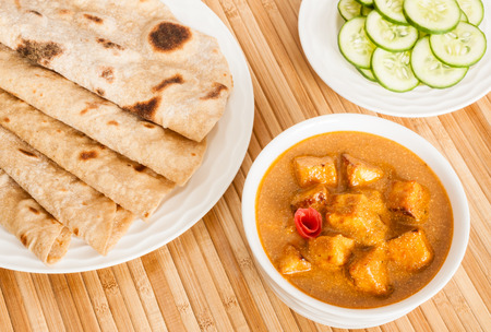 Chapati with Indian Paneer Butter Masala - Folded homemade wheat chapati (Indian bread) served with delicious Indian paneer butter masala and cucumber salad. It is prepared using paneer (cottage cheese), butter, tomato and various spices. photo
