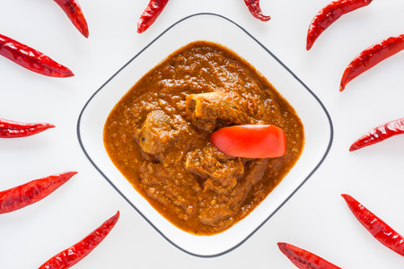 red chilli: Mutton rogan josh - Overhead view of delicious Indian mutton rogan josh with red chilli. This spicy hot Kashmiri dish uses red chilli cayenne pepper as its main ingredient. Natural light used. Stock Photo