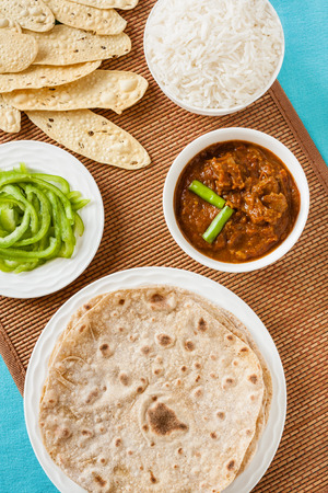 festive food: Mutton rogan josh meal - Overhead view of Indian mutton rogan josh meal with rice and chapati. This spicy hot Kashmiri dish uses red chilli cayenne pepper as its main ingredient. Natural light used. Stock Photo