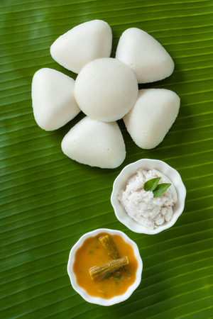 Indian idly served as a flower - Fresh steamed Indian Idly Idli  rice cake arranged decoratively as a flower on traditional banana leaf. Served with coconut chutney and sambar. Natural light used.