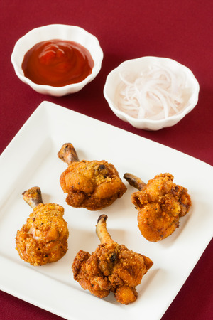 pollo: Piruletas de pollo frito con salsa de tomate - Vista de cerca de piruletas de pollo picantes fritos servidos con salsa de tomate y cadenas de cebolla cruda. DOF bajo. La luz natural utilizado.