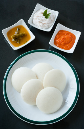 southern indian: Indian idly with chutney and sambar - A traditional south Indian breakfast of fresh steamed Indian Idly Idli  rice cake served with tomato chutney, coconut chutney and sambar. Natural light used. Stock Photo