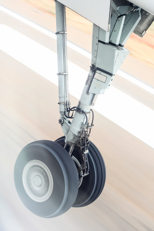 gear motion: Landing gear during takeoff - The landing gear of an aircraft captured at the moment of takeoff against a blurred runway. Stock Photo