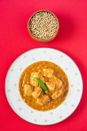indian food: Indian chicken curry - Overhead view of spicy Indian chicken curry served on a plate pictured next to a bowl of coriander seeds, a key ingredient. Natural light used. Stock Photo