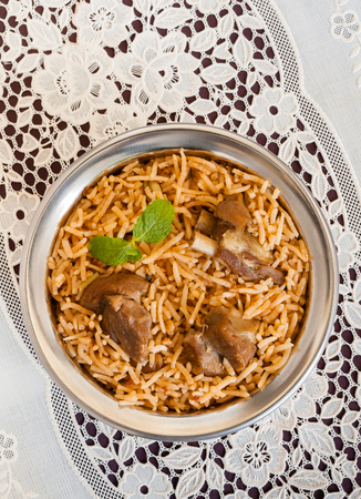 biryani: Mutton biryani overhead view - Overhead view from the top of delicious mutton lamb biryani with mint garnish and served in authentic copper bowl. Natural light used.