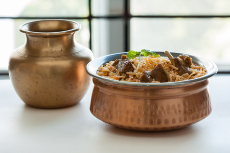 bowl: Mutton biryani - Closeup view of delicious mutton lamb biryani with mint garnish and served in authentic copper bowl. Natural light used.