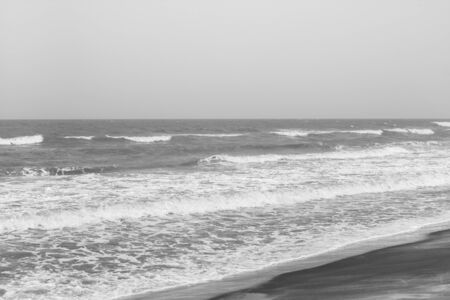 frothy: Frothy waves on beach with patterns - Incoming frothy sea waves on a tropical beach. These rushing waves leave curved patterns on the beach. Black and white image.