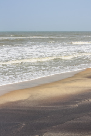 silt: Frothy waves on beach with patterns - Incoming frothy sea waves on a tropical beach. These rushing waves leave curved patterns on the beach with orange sand and black silt deposits from the sea. Stock Photo