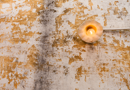 Incandescent light bulb on old wall - A bright lit incandescent light bulb with yellow filament on an old chipped wall. Stock Photo