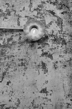 Incandescent light bulb on old wall - A bright lit incandescent light bulb on an old chipped wall. Stock Photo