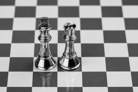 King and Queen - Rugged brass chess king and queen pieces on a chess board. Stock Photo