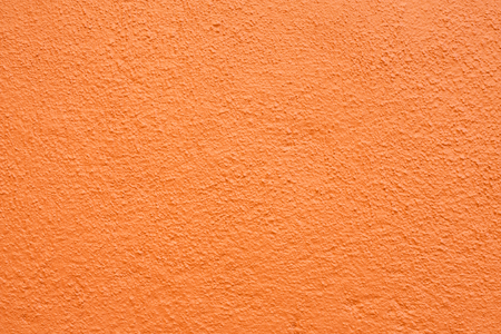 Stucco wall - Orange stucco textured wall background with natural light.