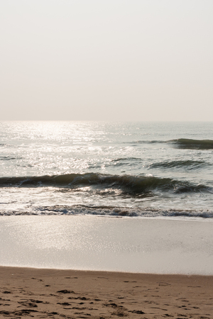 Glistening waves on beach - Glistening sea waves on a tropical beach in the morning. Stock Photo