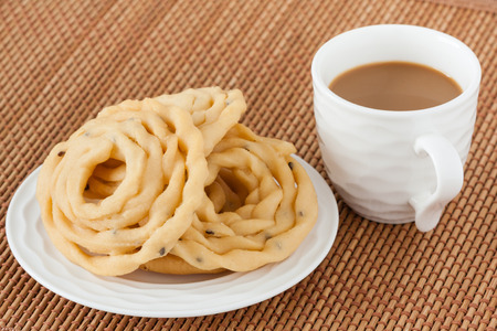 Indian murukku snack with coffee - A closeup of traditional deep fried Indian snack murukku on a plate served with coffee.