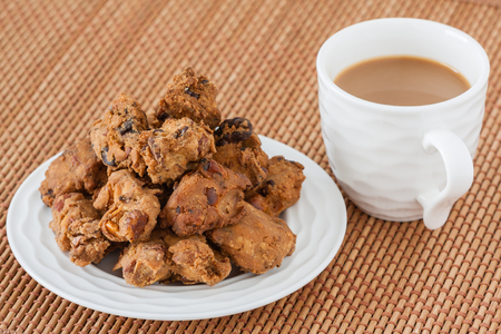 Indian pakoda snack with coffee - A macro closeup of traditional deep fried Indian snack pakkoda on a plate served with coffee. A variety of nuts and flour is used to prepare it.