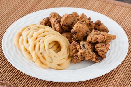 Indian murukku and pakoda snack - A closeup of traditional deep fried Indian snacks murukku and nuts pakkoda on a plate. Stock Photo
