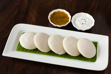 Indian idly with chutney and sambar - Fresh steamed Indian Idly (Idli / rice cake) arranged on banana leaf lined plate. Served with coconut chutney and sambar. Natural light used.