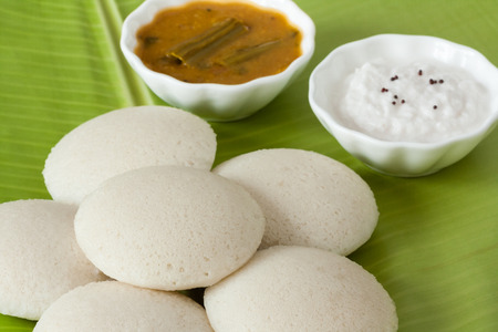 Indian idly with chutney and sambar - Fresh steamed Indian Idly (Idli / rice cake) arranged on a traditional banana leaf. Served with coconut chutney and sambar. Natural light used.