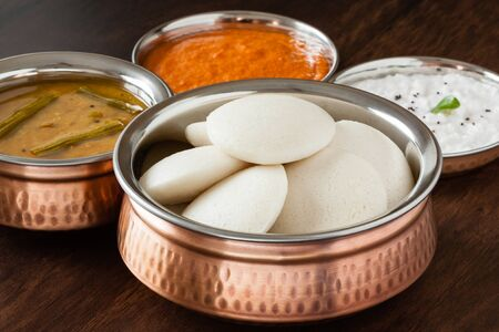 Indian idly with chutney and sambar - Fresh steamed Indian Idly (Idli / rice cake) arranged in authentic copper bowl. Served with tomato chutney, coconut chutney and sambar. Natural light used.