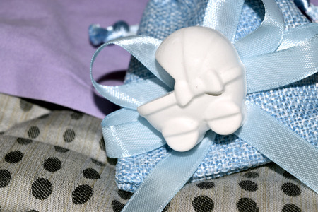 favor: blue bag with confetti and decoration of a cradle shape