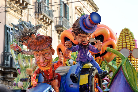 Acireale (CT), Italy - February 28, 2017: allegorical float, depicting two men with colored dress and hat one red and one purple, during the carnival parade along the streets of Acireale.