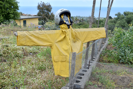 Extravagant scarecrow realized with a helmet and raincoat