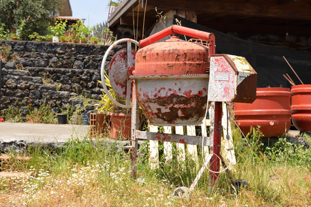 Old rusty cement mixer on construction site