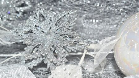 close up of a composition of Christmas decorations on silvery background