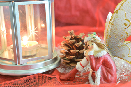 close up of a christmas fairy with various decorations on red background
