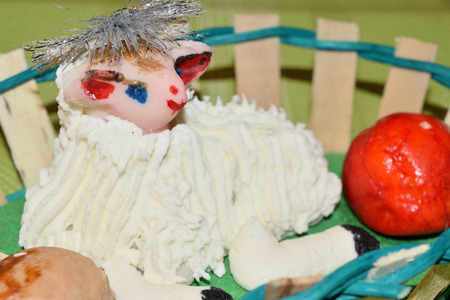 close up of marzipan Easter lamb and fruit in a basket
