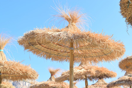 Straw parasols at the beach in summer