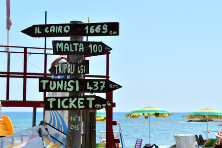 Multidirectional sign with mileage to distant cities and ticket office