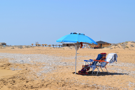 isolated beach umbrella and deck chairs on the beach in summer Reklamní fotografie