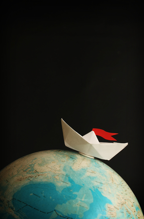 Travel concept with globe and paper boat