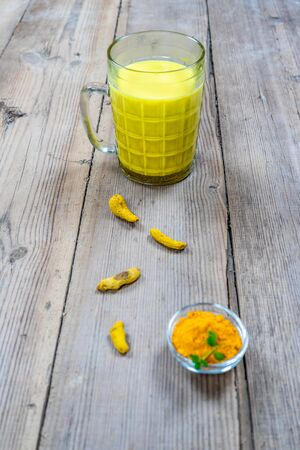 Golden milk in a glass cup on a wooden background